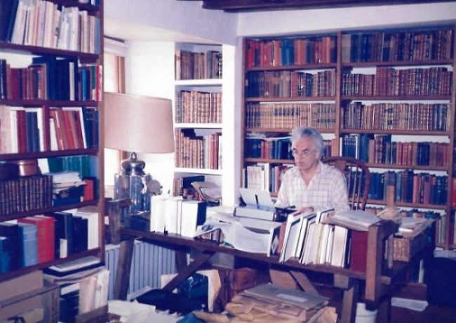 Ian Robertson at his desk, surrounded by books